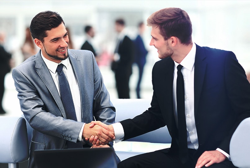 Two men in business suits shaking hands